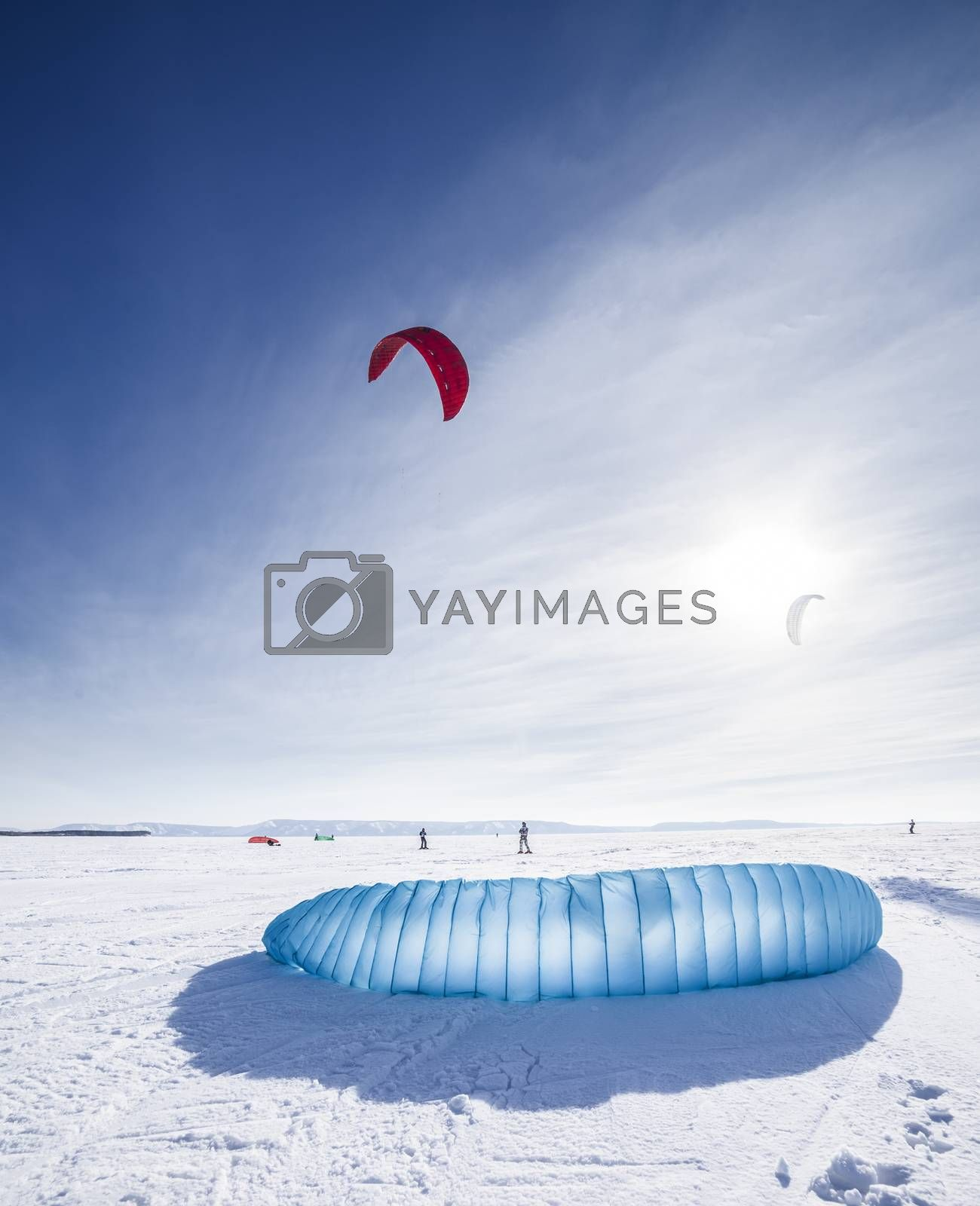 Royalty free image of Kiteboarder with blue kite on the snow by H2Oshka