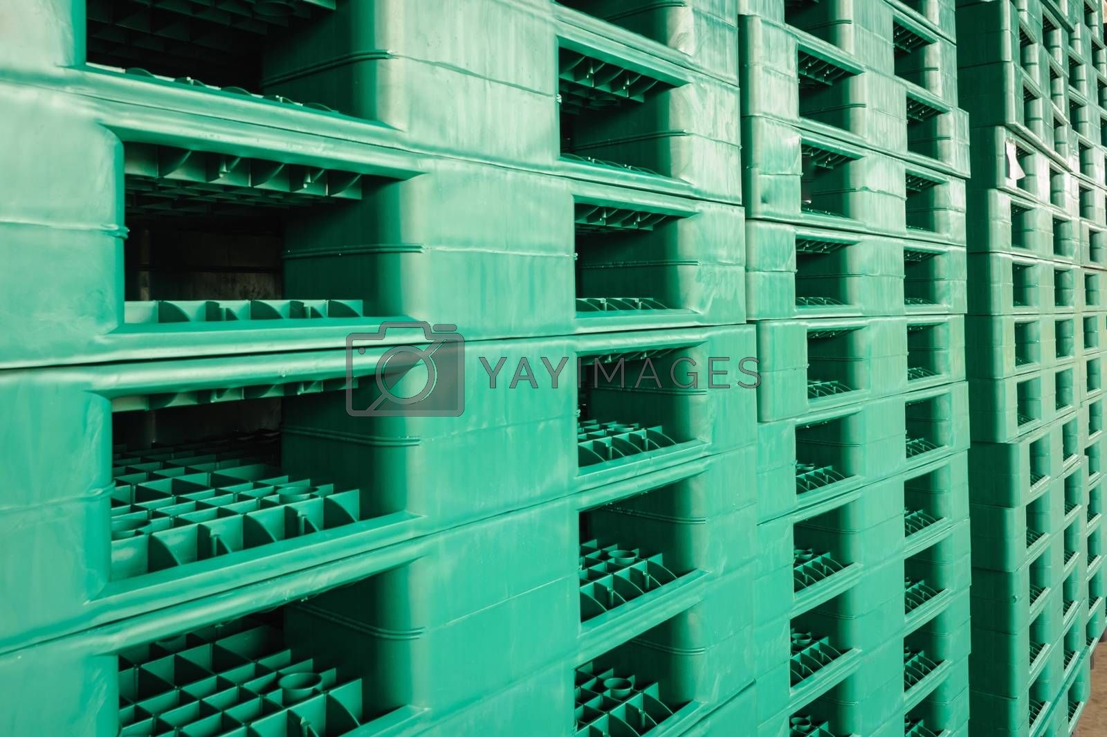 Green plastic pallets in warehouses, sorted and delivered.