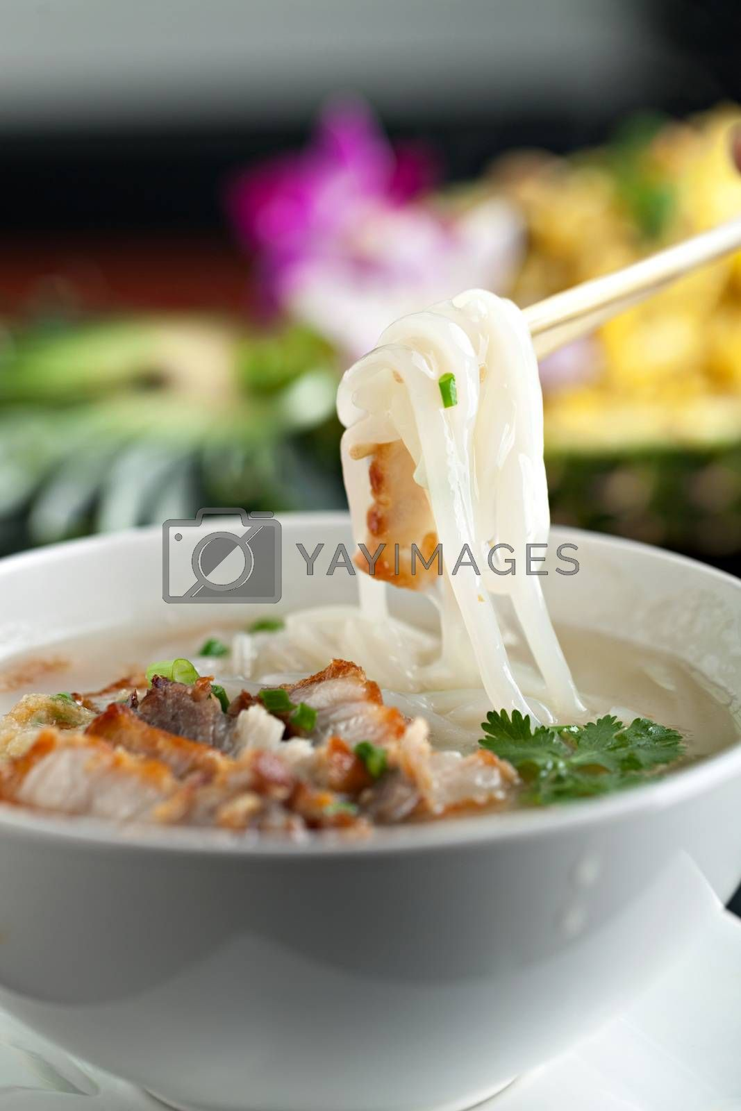 Closeup of a person eating Thai style crispy pork rice noodle soup from a bowl with chopsticks. Pineapple fried rice in the background.