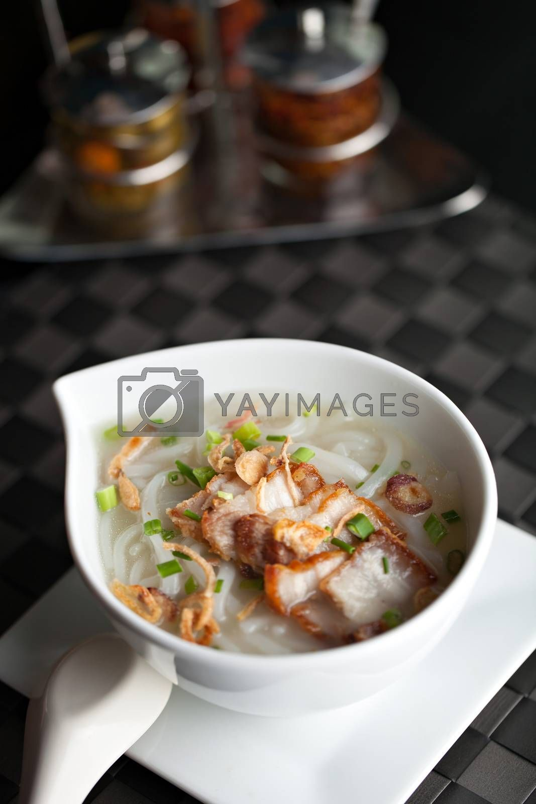 Closeup top down view of Thai style crispy pork rice noodle soup in a bowl with copy space.