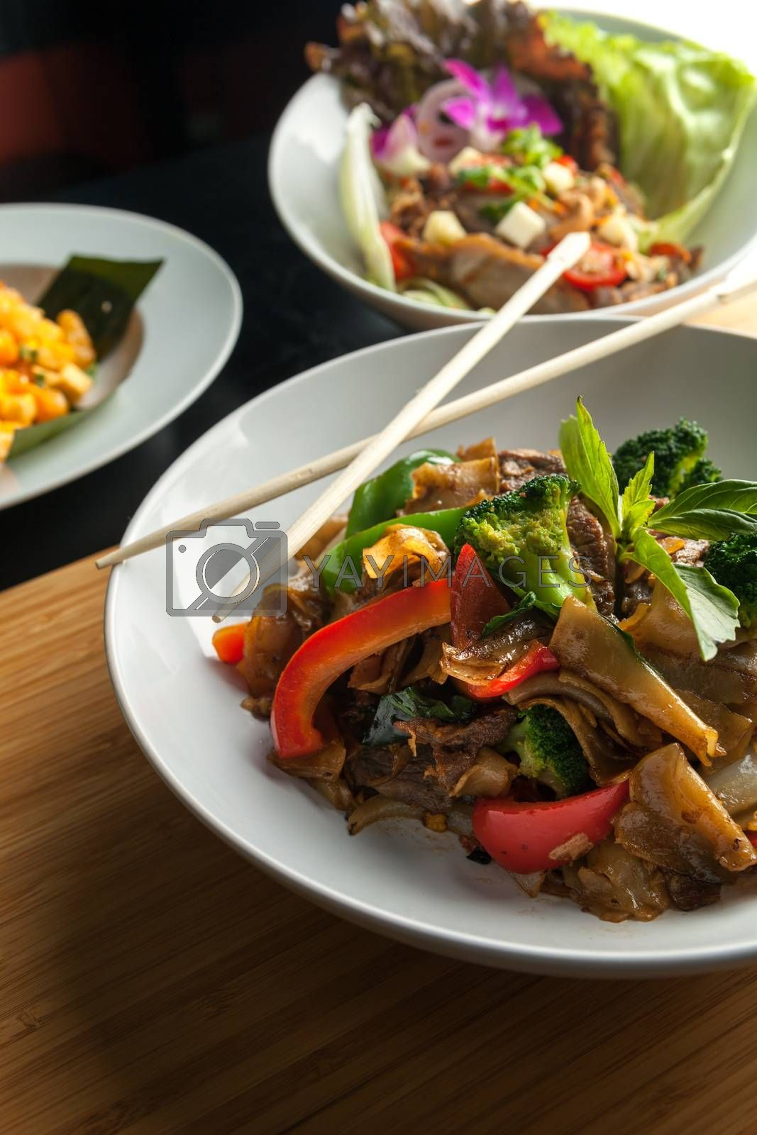 Pad kee mao drunken noodle thai dish with beef and mixed vegetables.