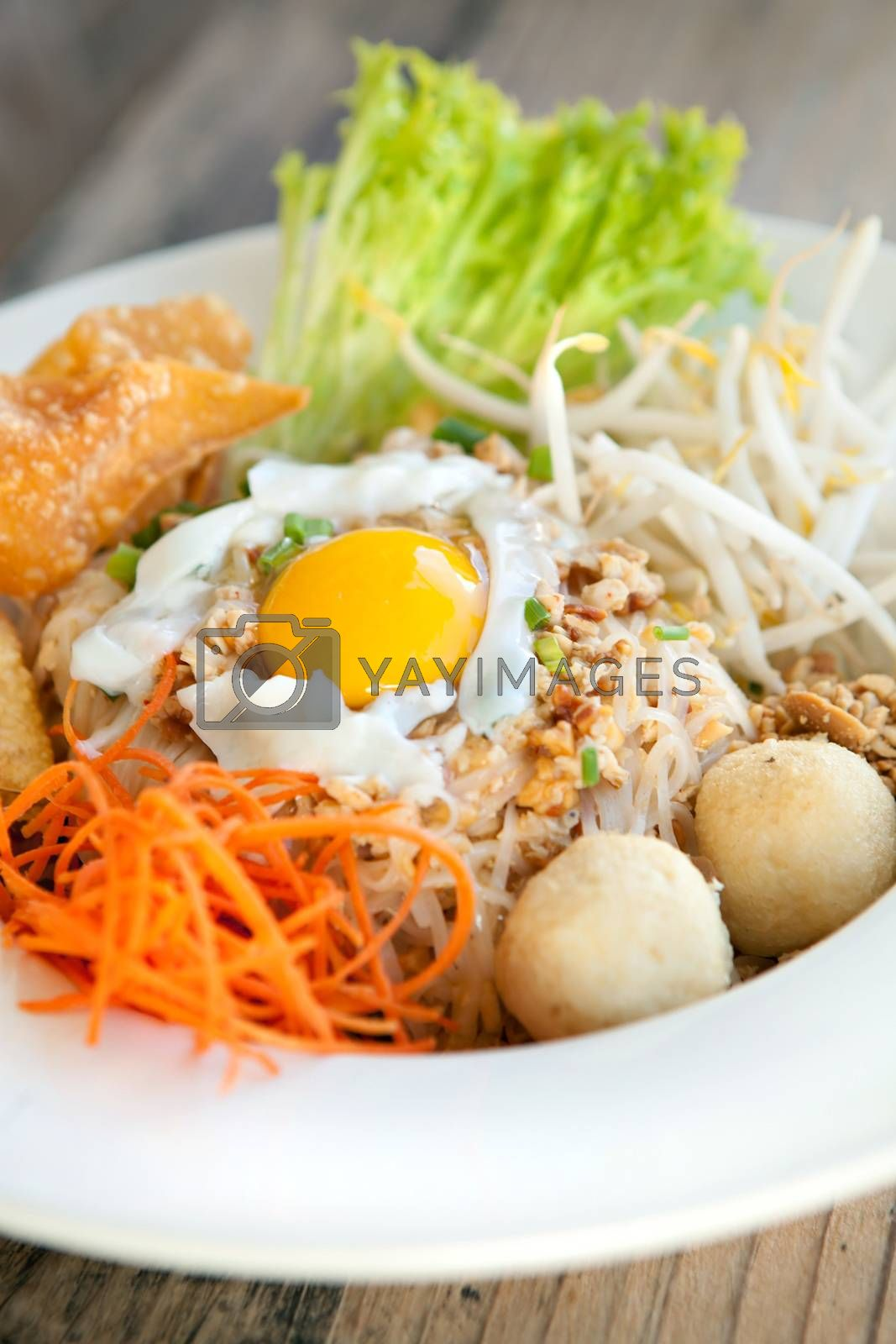 Gai pad bai gaprow style Thai dish with fried egg and rice noodles.