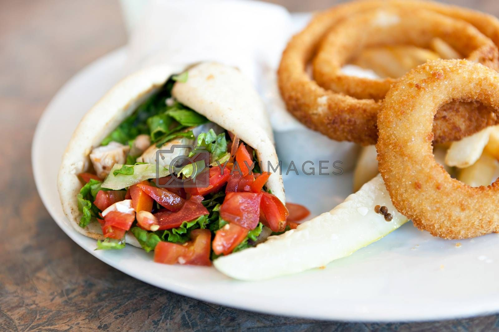 Chicken pita wrap sandwich with onion rings and a deli pickle slice. Shallow depth of field.