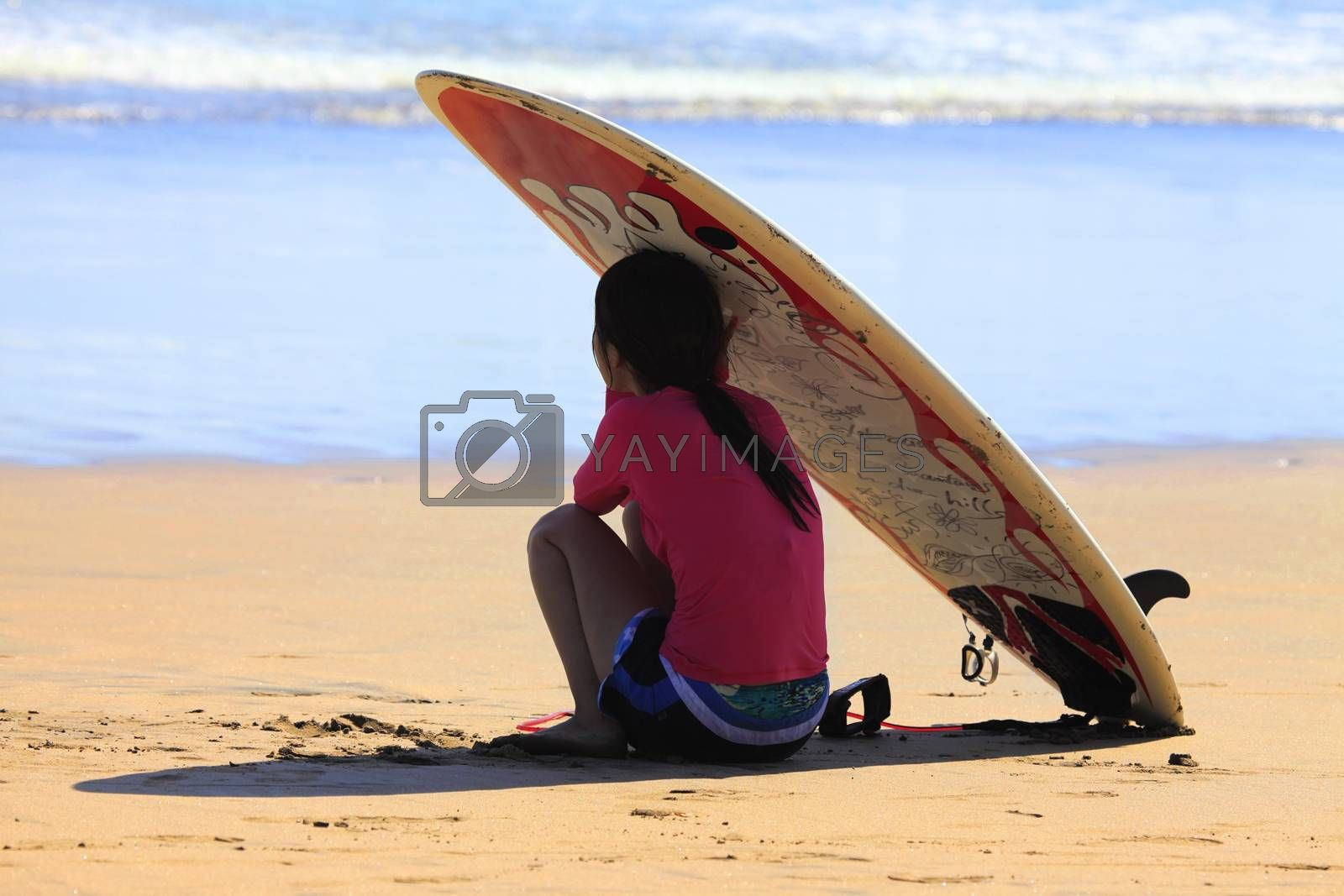 Bali, Indonesia - July 15, 2010: unknown surfer girl resting on the ocean. Kuta, Bali