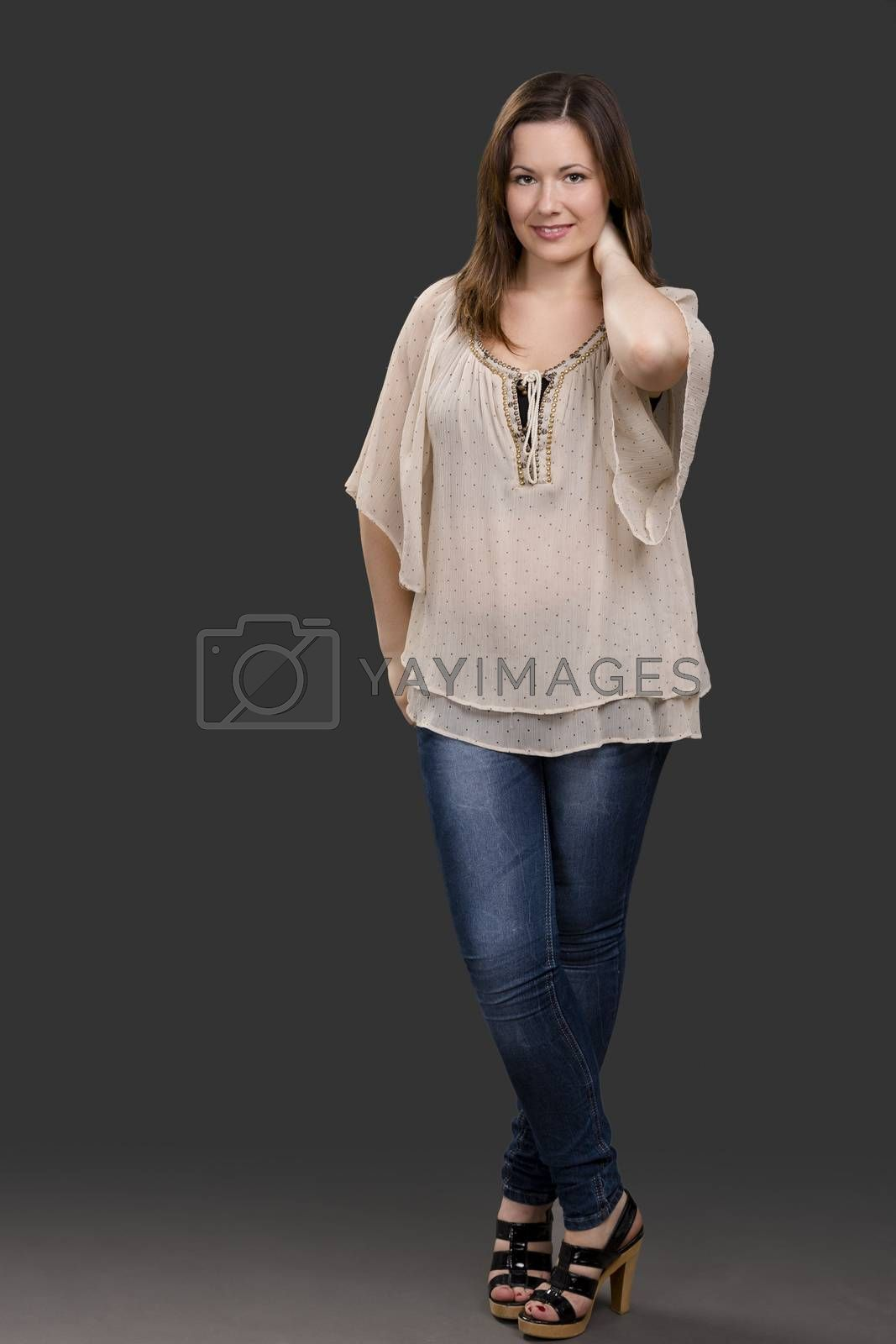 Beautiful young woman posing in a grey background