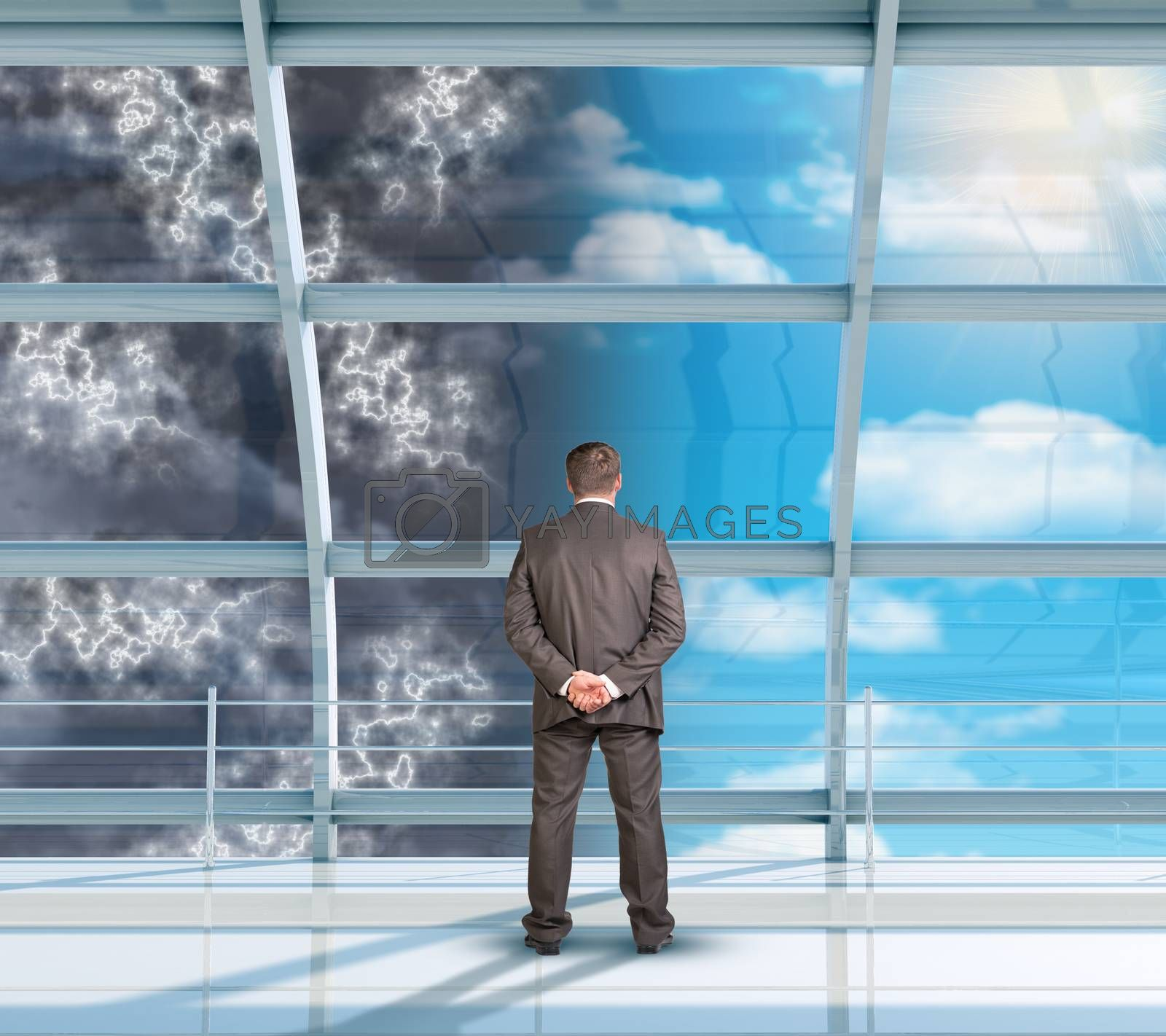 Businessman looking at changing weather through window, rear view
