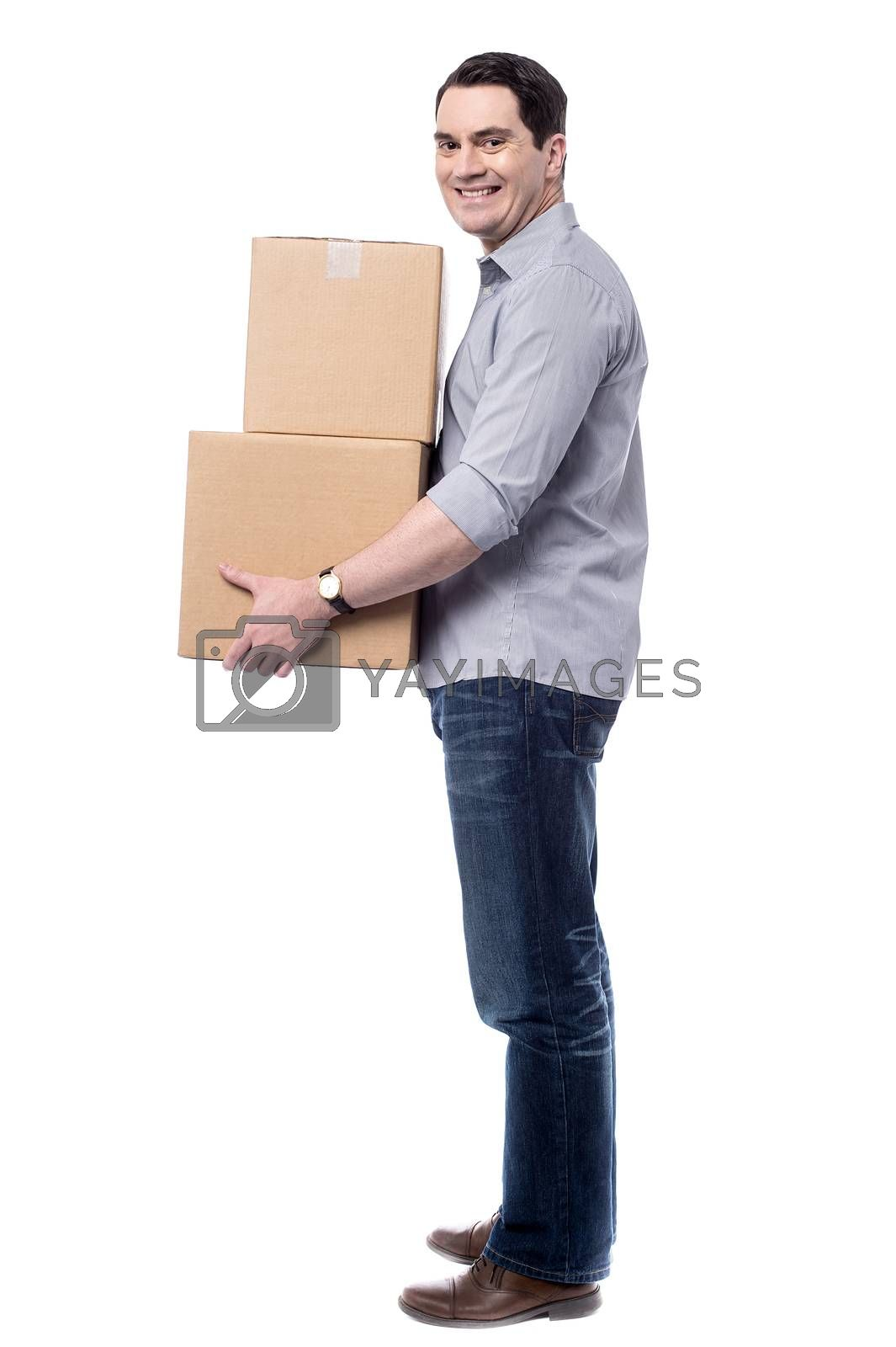 Sideways of casual man handling cardboard boxes
