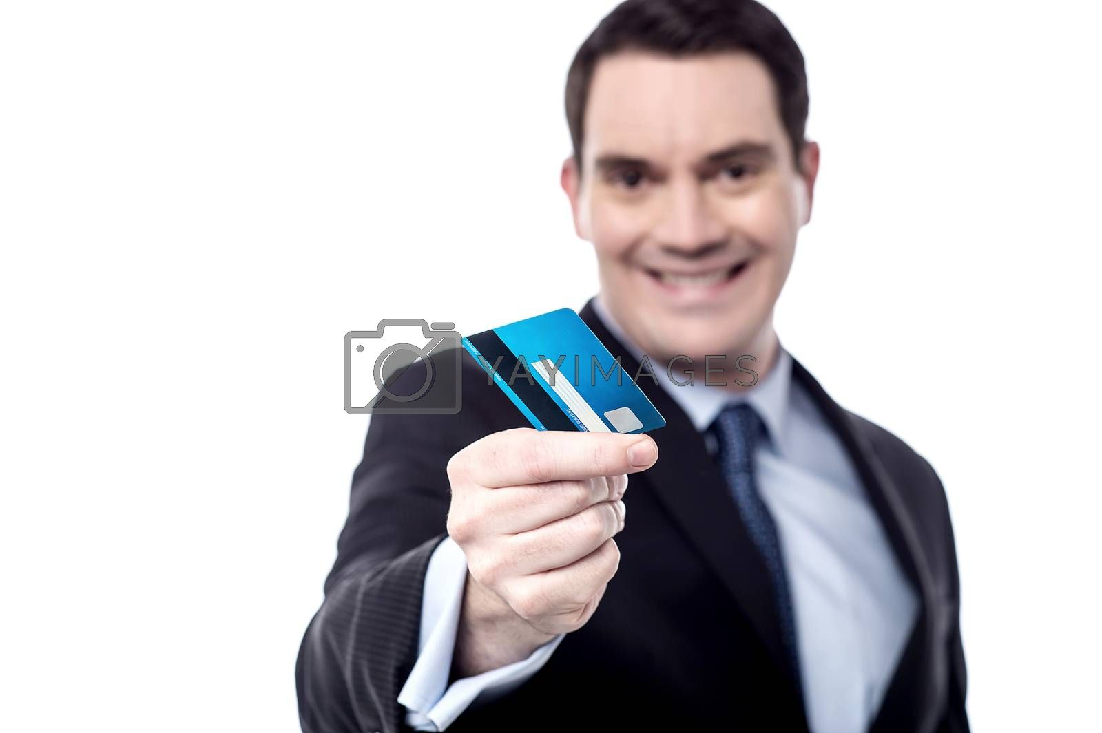 Smiling businessman offering his credit card over white