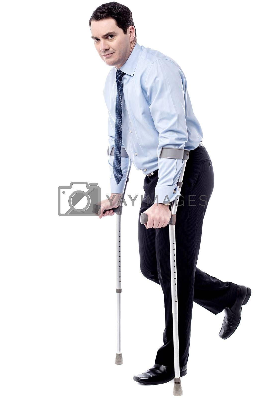 Businessman trying to walk with crutches over white