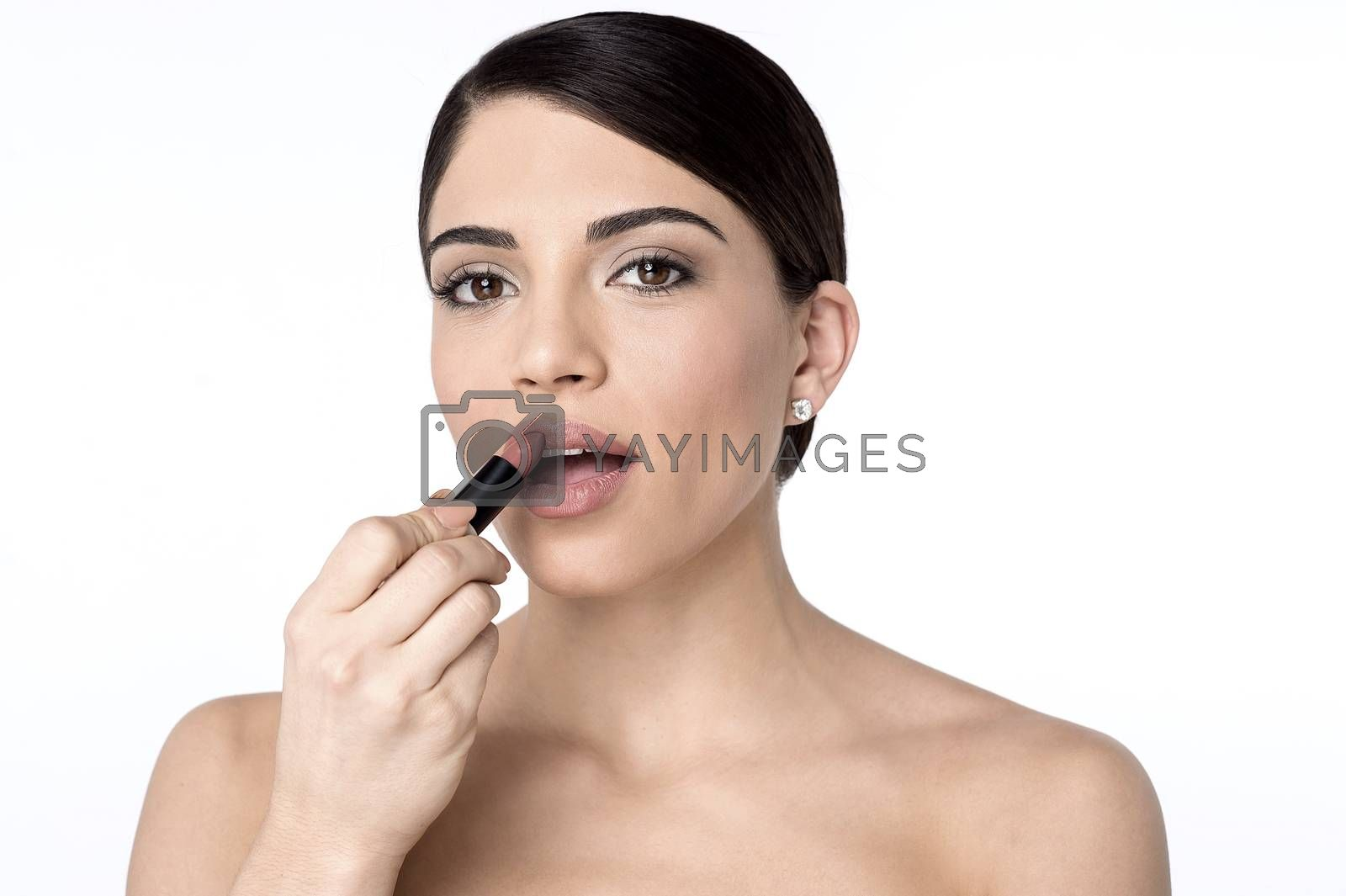 Pretty woman applying lipstick on her lips