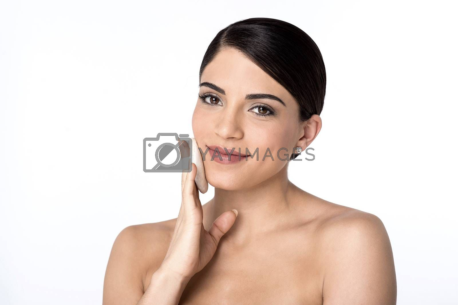 Young woman applying cosmetic powder puff on her face