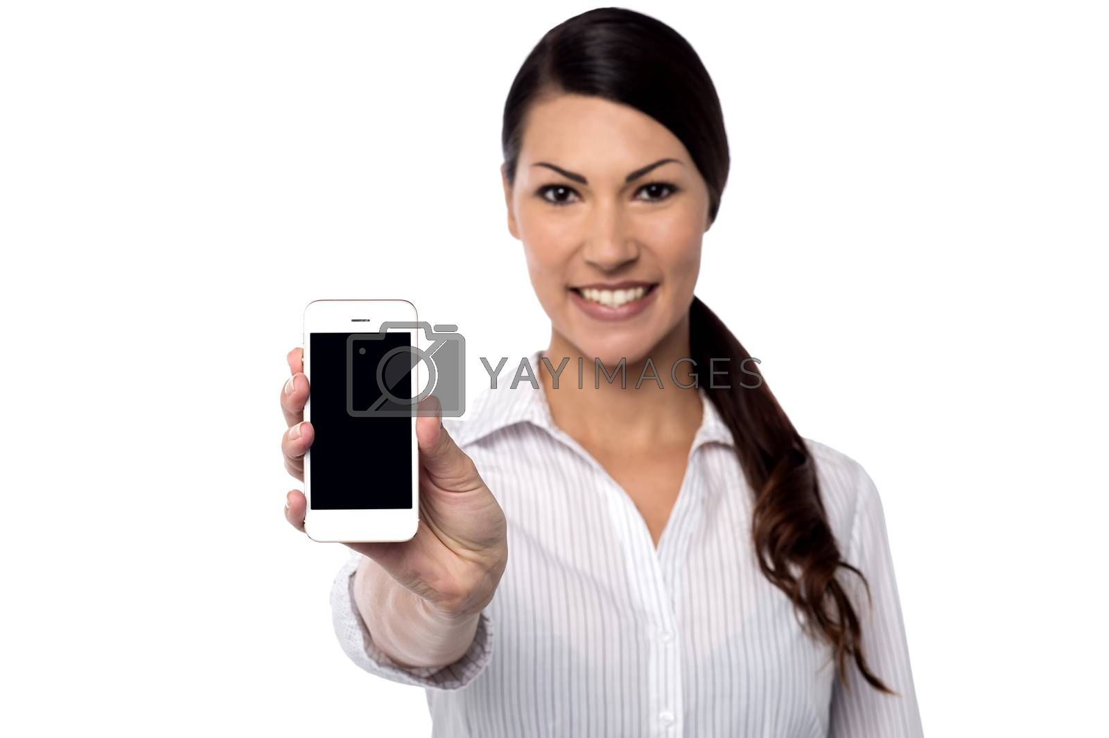 Female executive showing mobile phone to camera