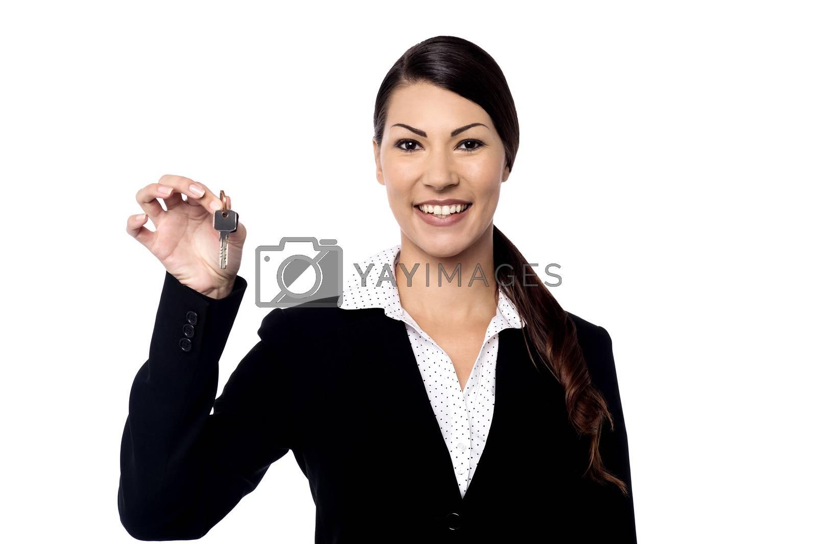 Beautiful female realtor showing a house key