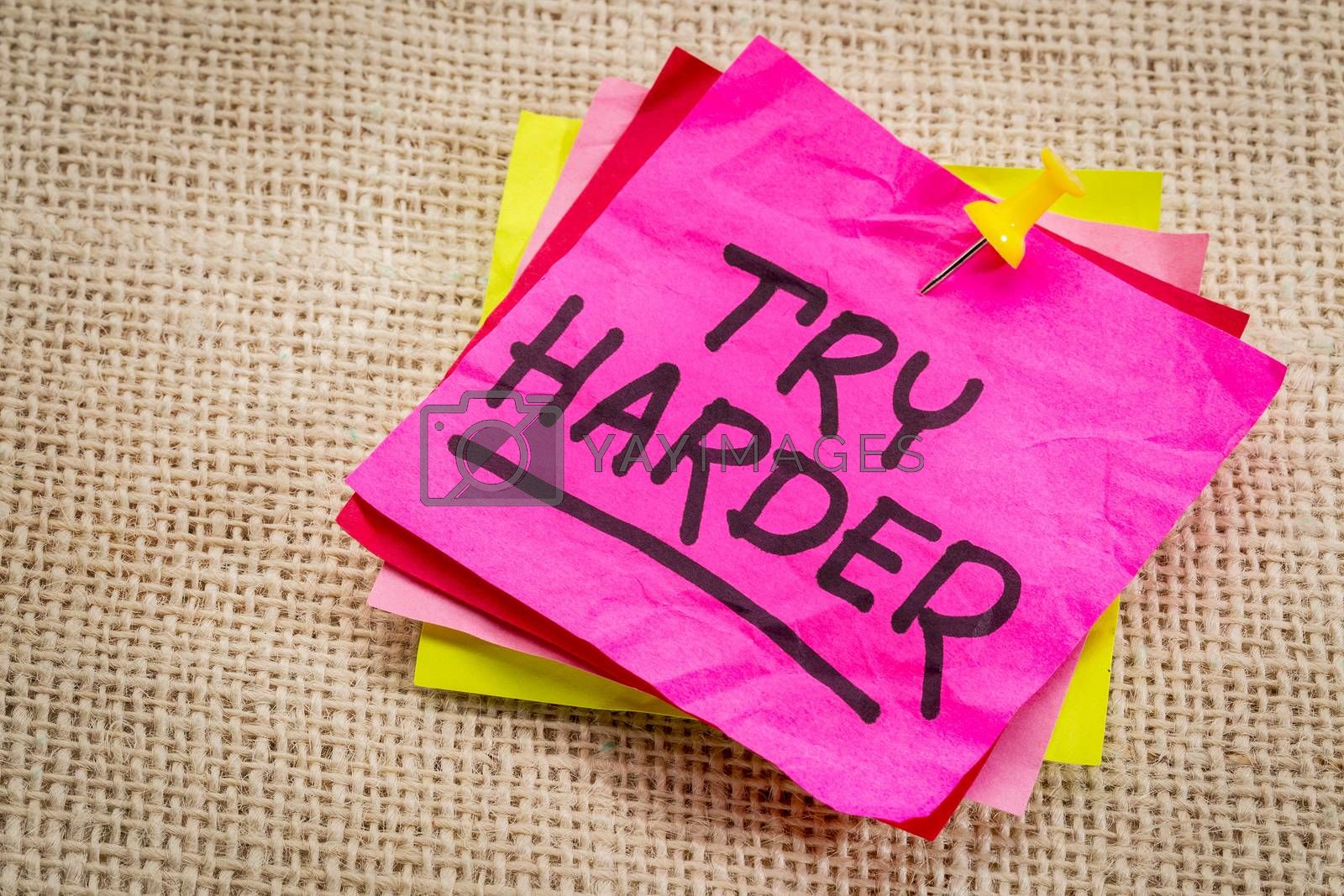 try harder - motivation words on a  purple sticky note against burlap canvas
