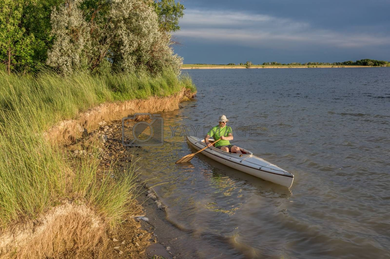 male paddler paddling a decked expedition canoe on a lake in northern Colorado