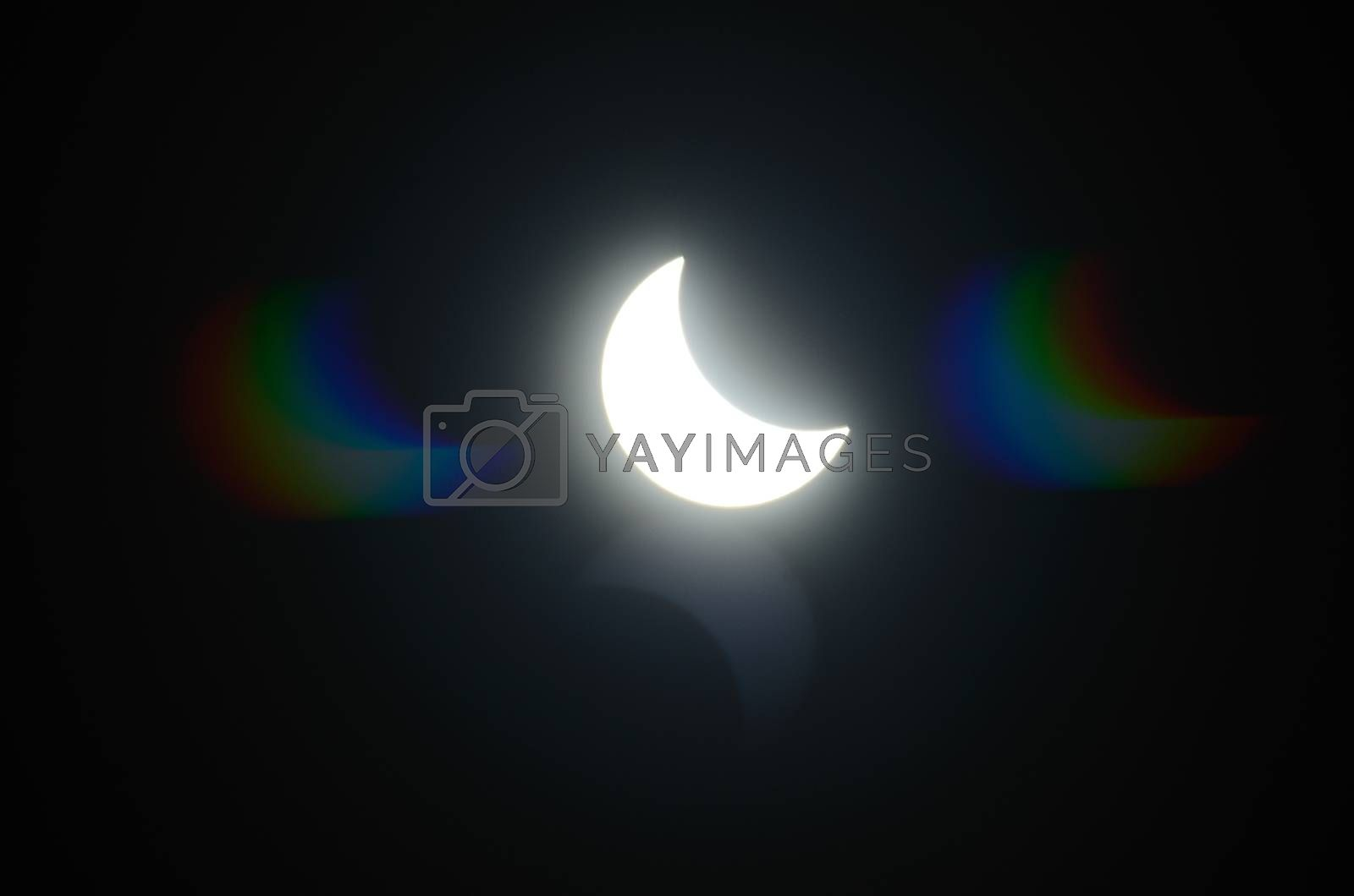 very bright shining solar eclipse with colorful reflection