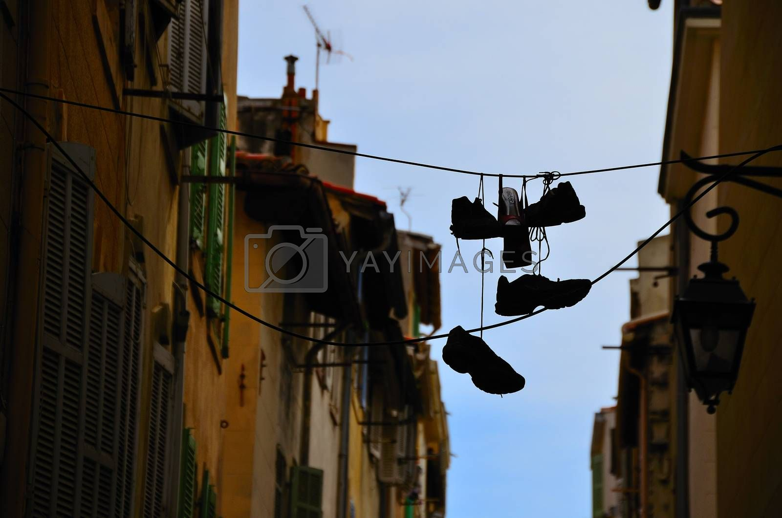 shoes hanging between houses in the city of marseille