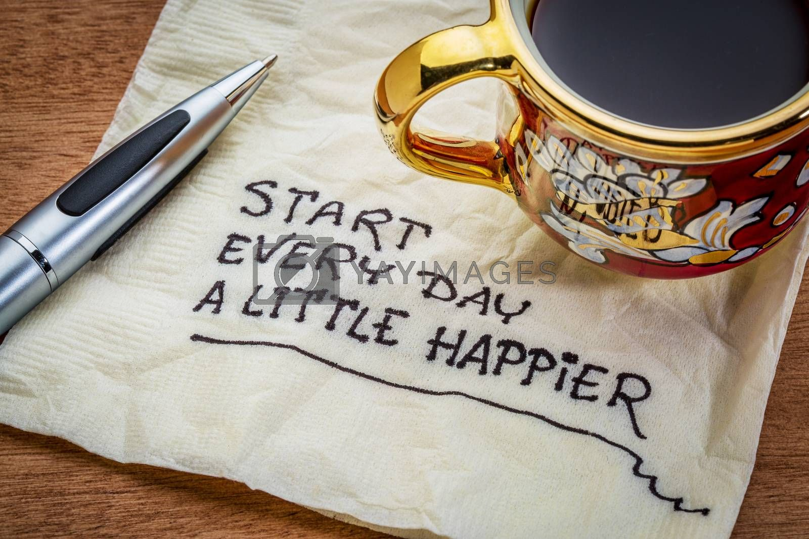 Start every day a little happier - happiness and attitude concept - handwriting on a napkin with cup of coffee