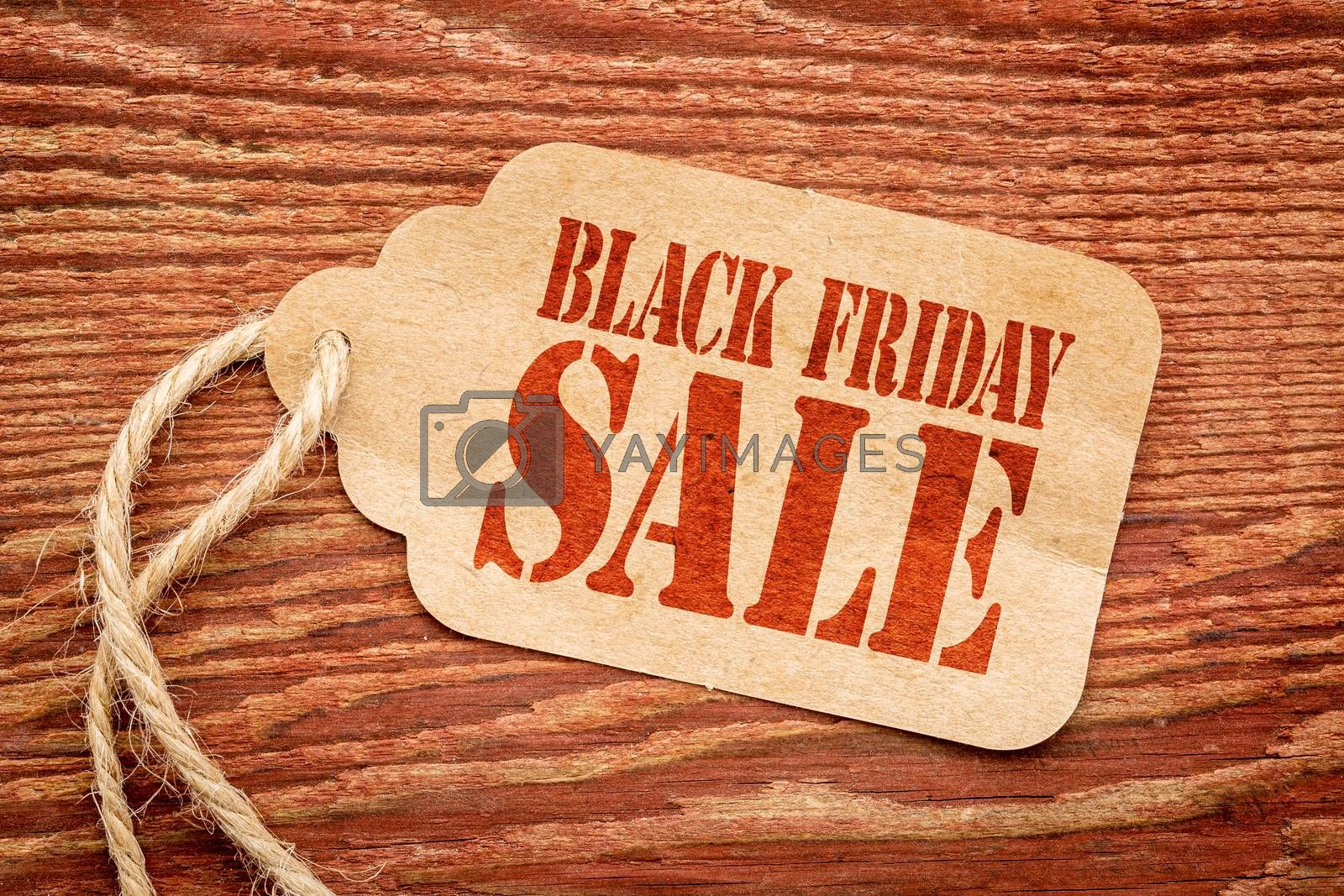 Black Friday sale sign a paper price tag against rustic red painted barn wood