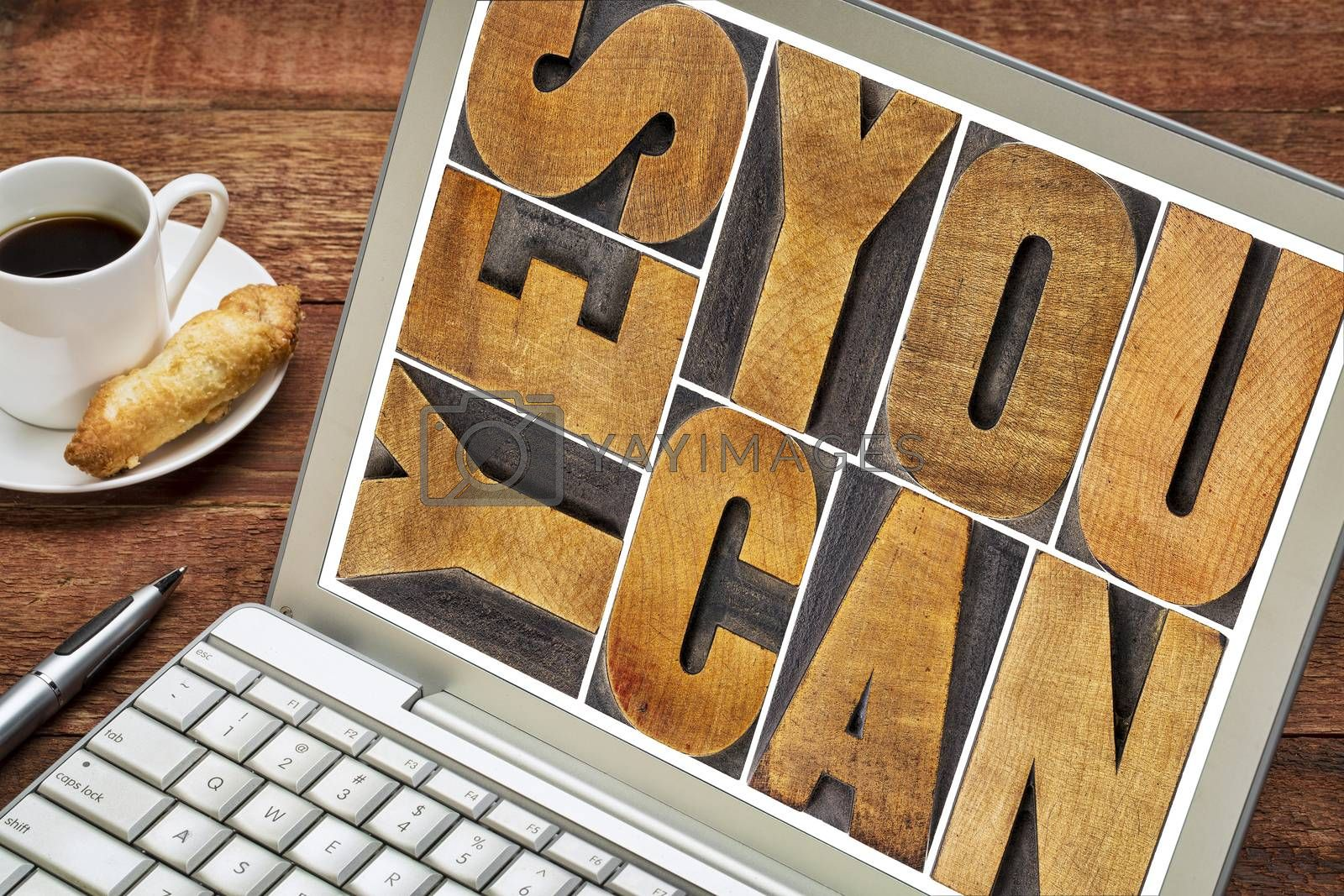 Yes you can - motivational slogan - a  text in vintage letterpress wood type printing block on a laptop screen with a cup of coffee