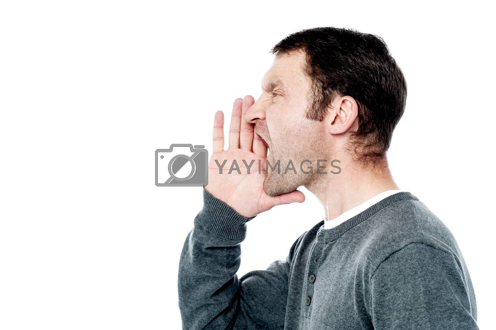 Side pose of man shouting, hands near his mouth.