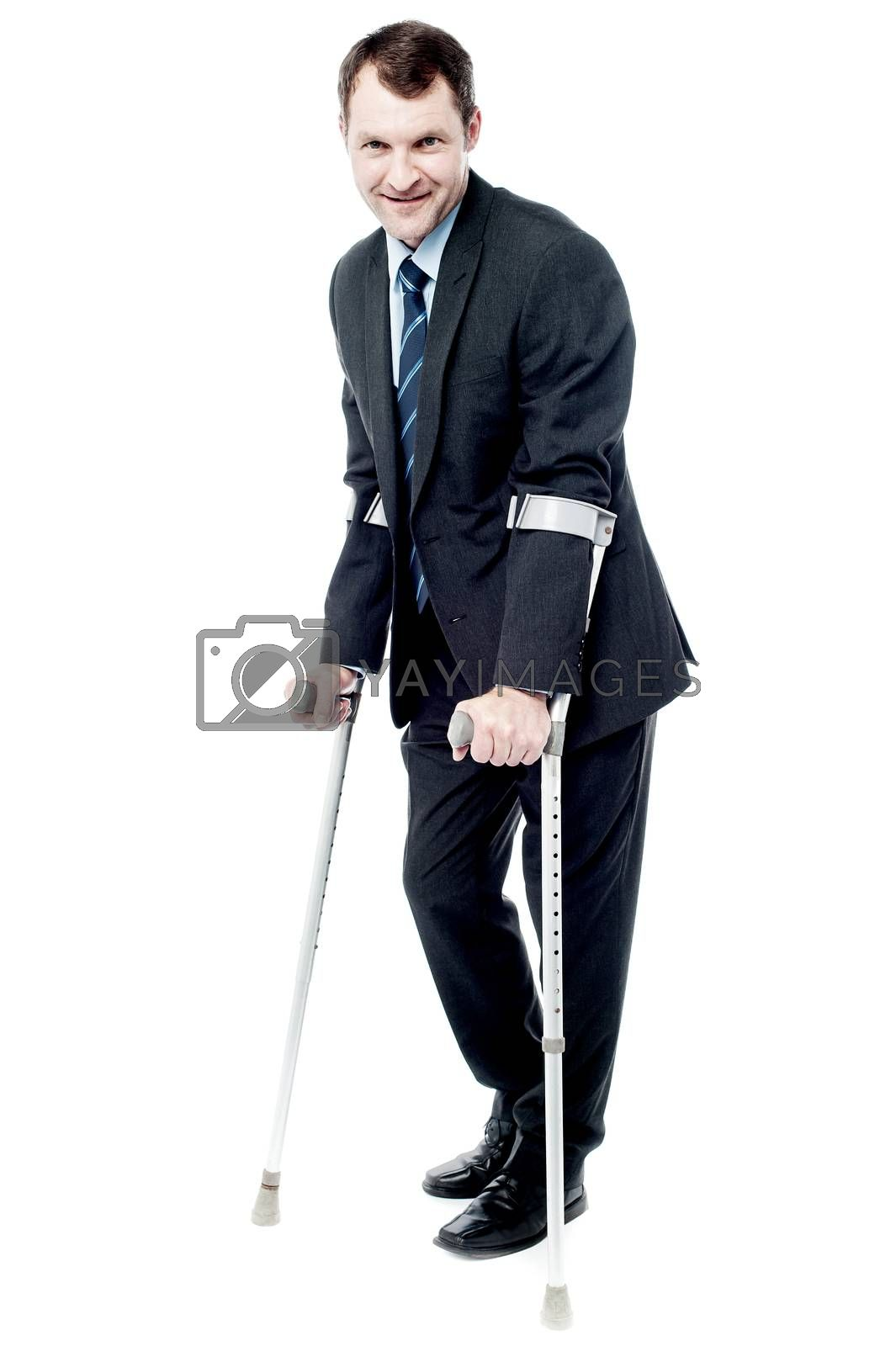 Confident businessman walking with crutches