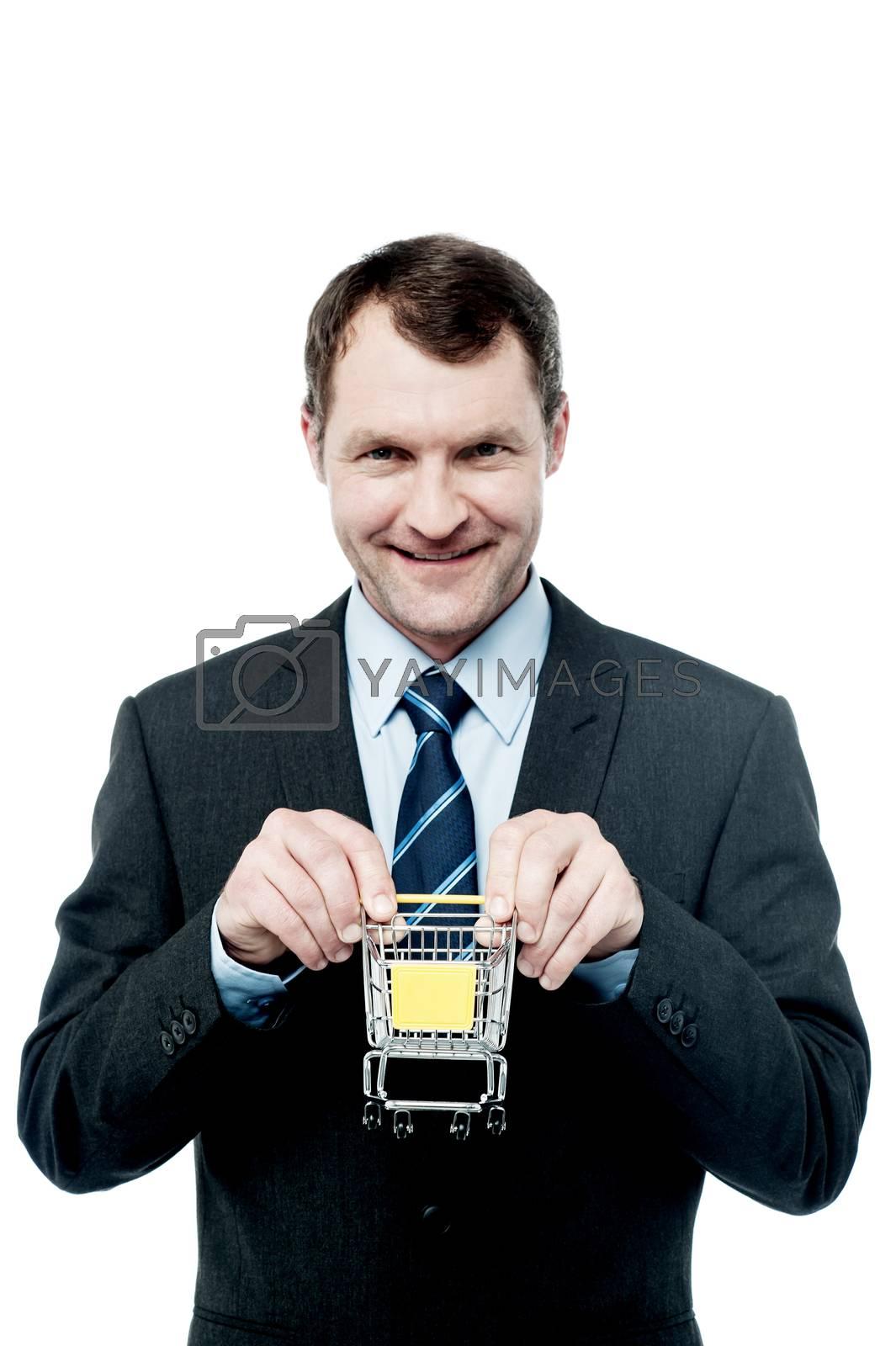 Happy businessman showing mini shopping cart