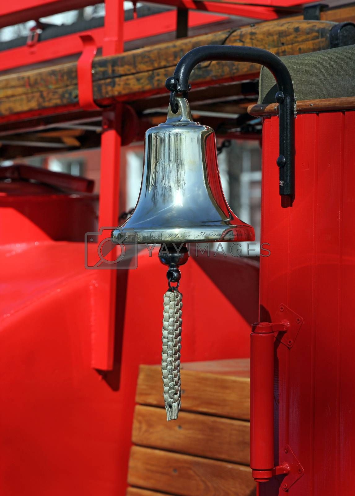 Metal alarm bell on red fire truck.