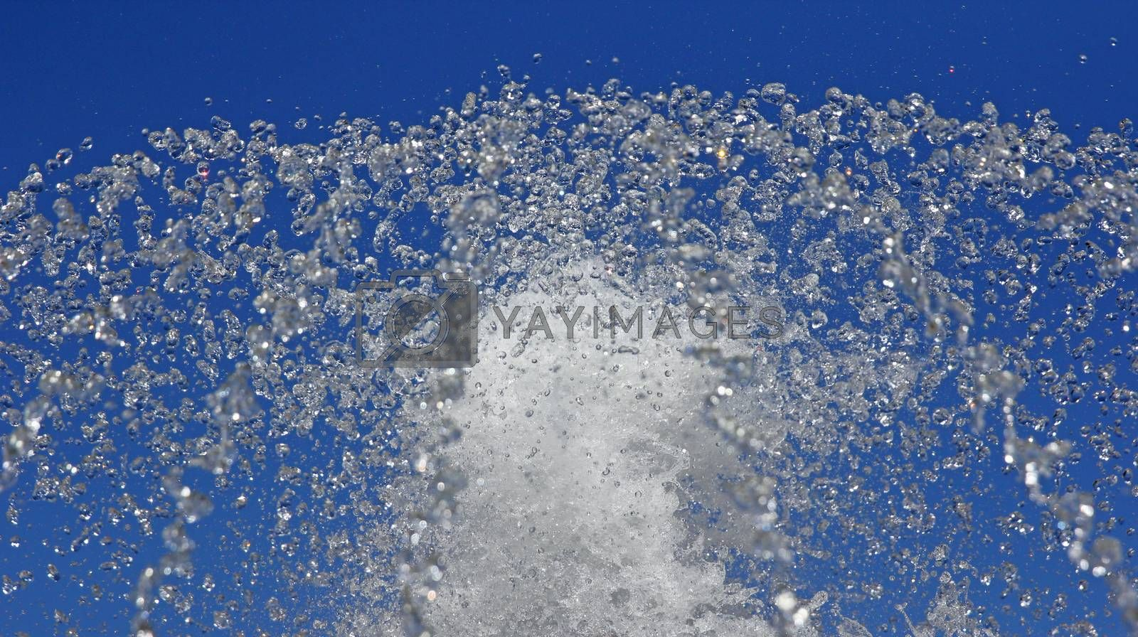 Fountain drops of pure water against a blue sky.
