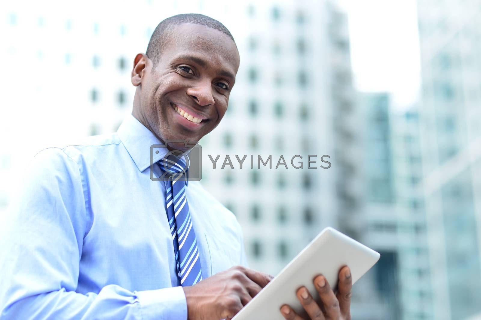 Smiling male corporate executive using his tablet pc
