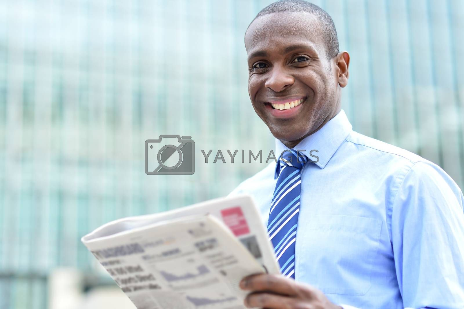 Corporate male smiling with magazine at outdoors