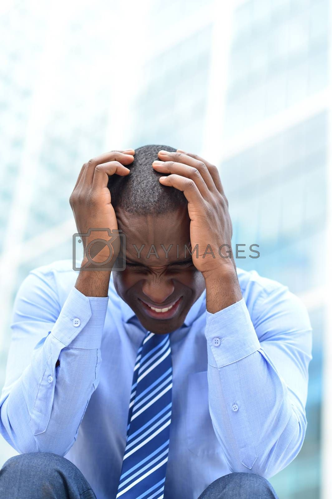 Frustrated businessman sitting in office steps