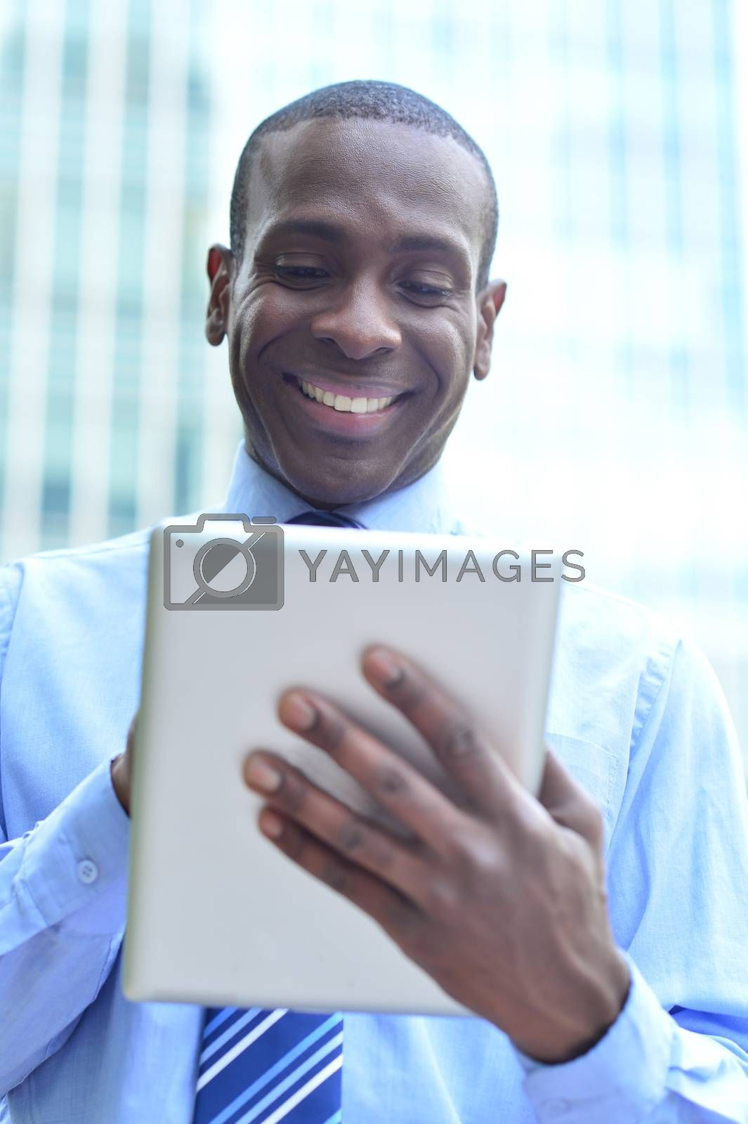 Smiling male executive working in his digital tablet