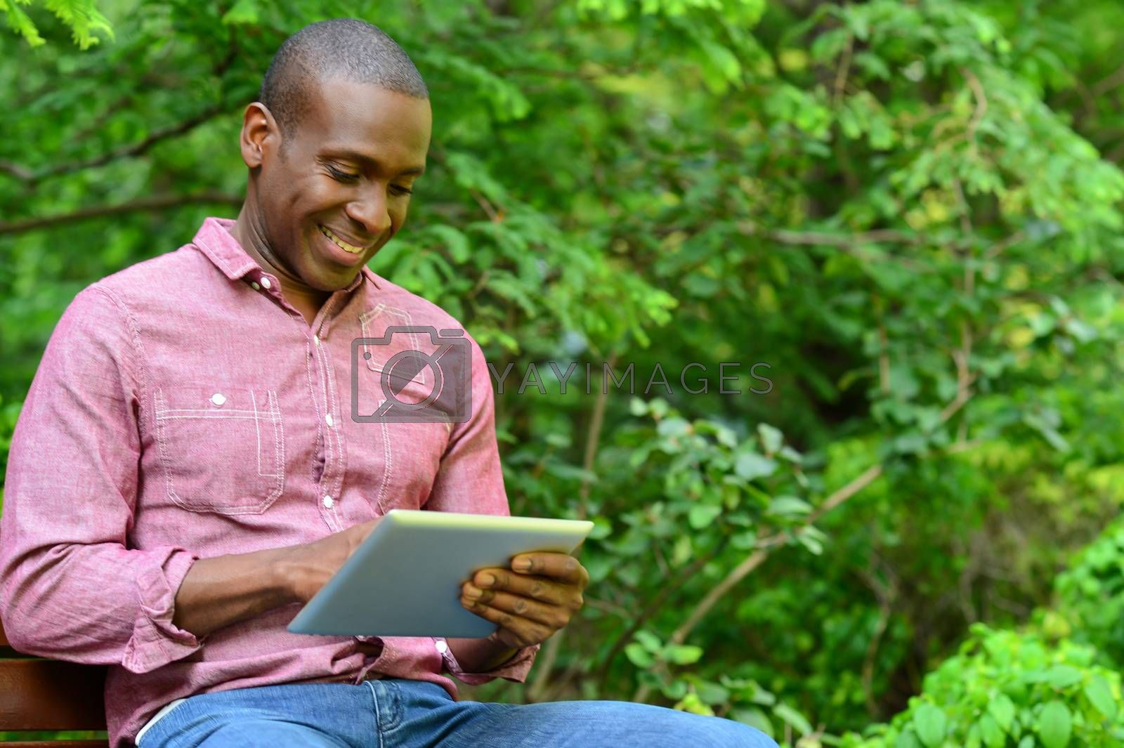 Happy male using his tablet pc at outdoors
