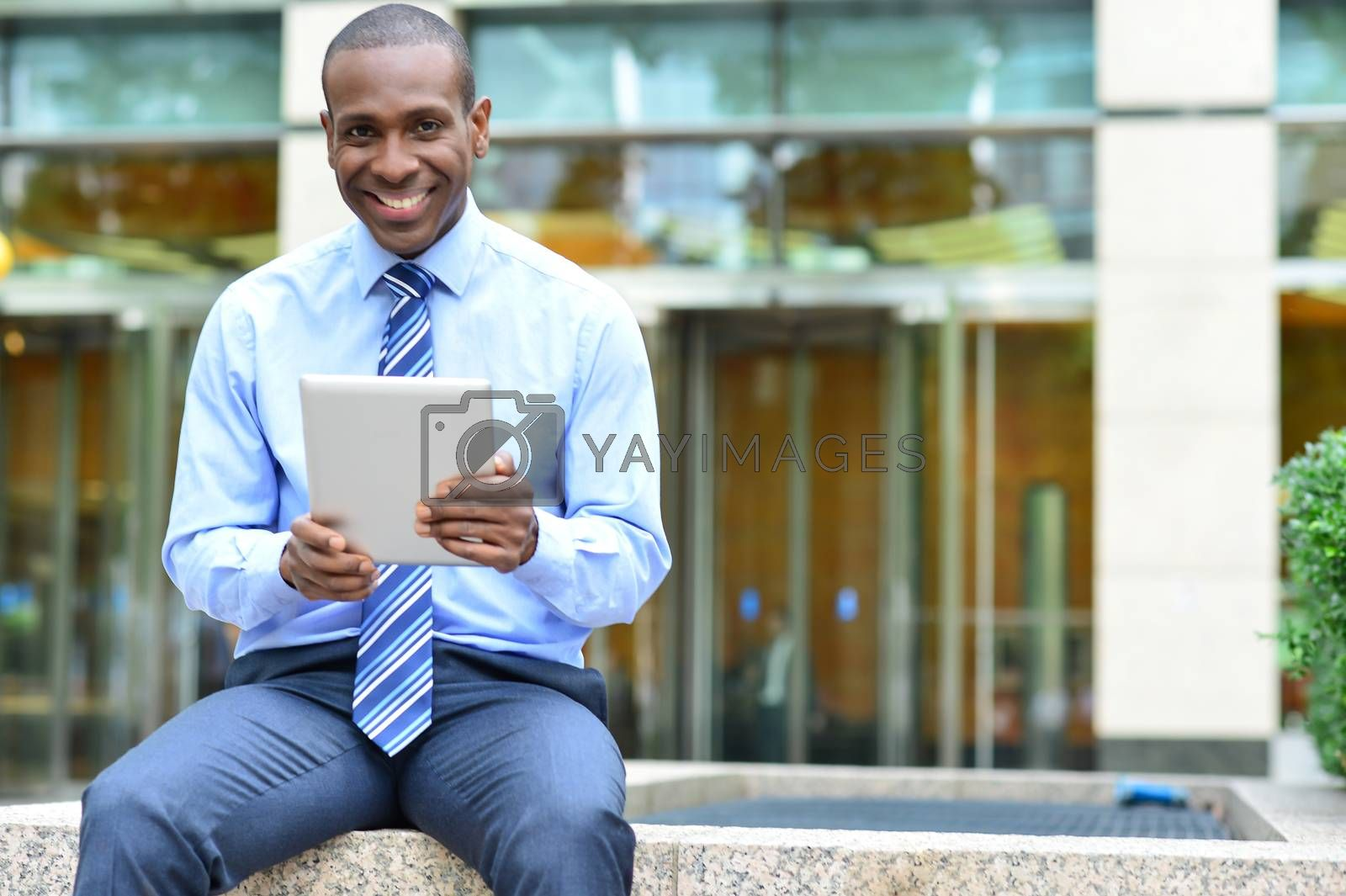 Corporate male siting outdoors with his new tablet pc