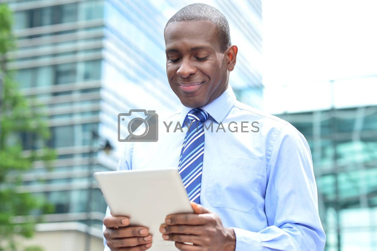 Happy businessman checking mails in tablet