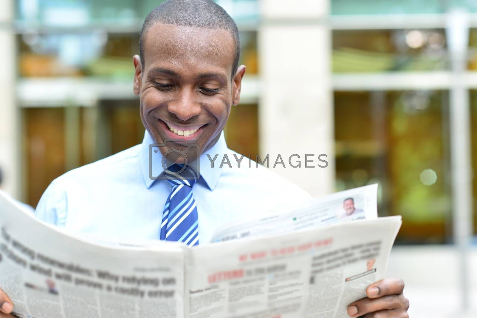 Happy male executive reading a newspaper