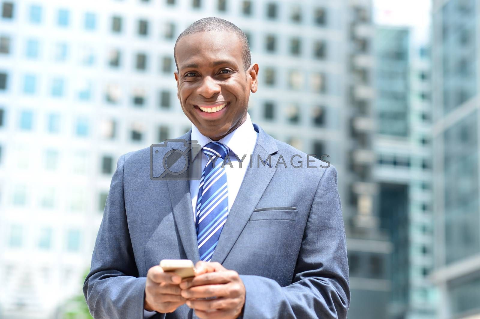 Smiling businessman posing with his mobile phone