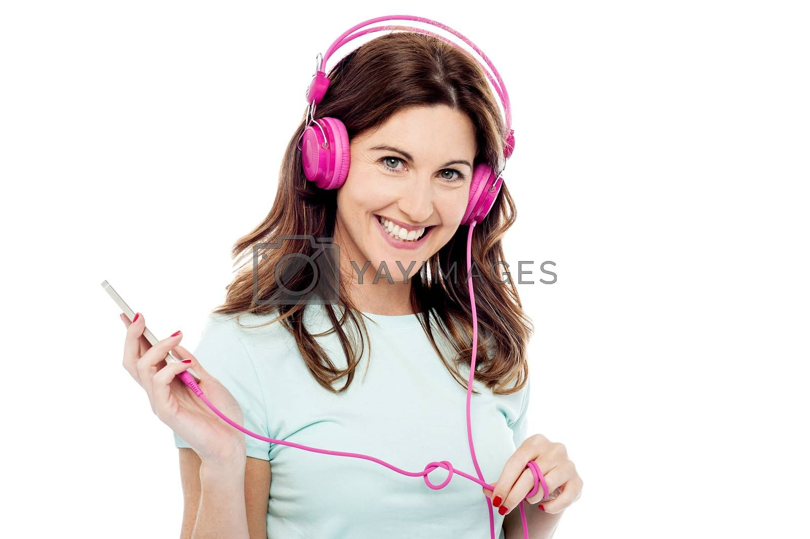 Happy woman listening music from mobile phone
