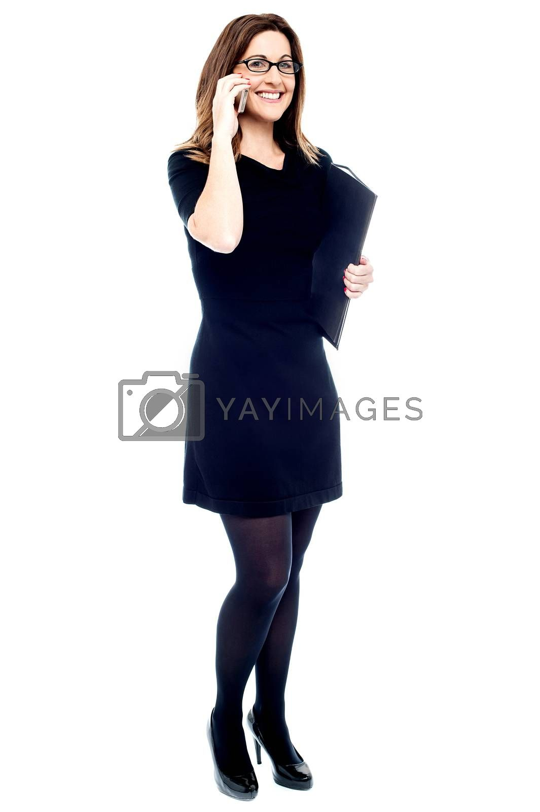 Corporate woman with files, talking on mobile phone.
