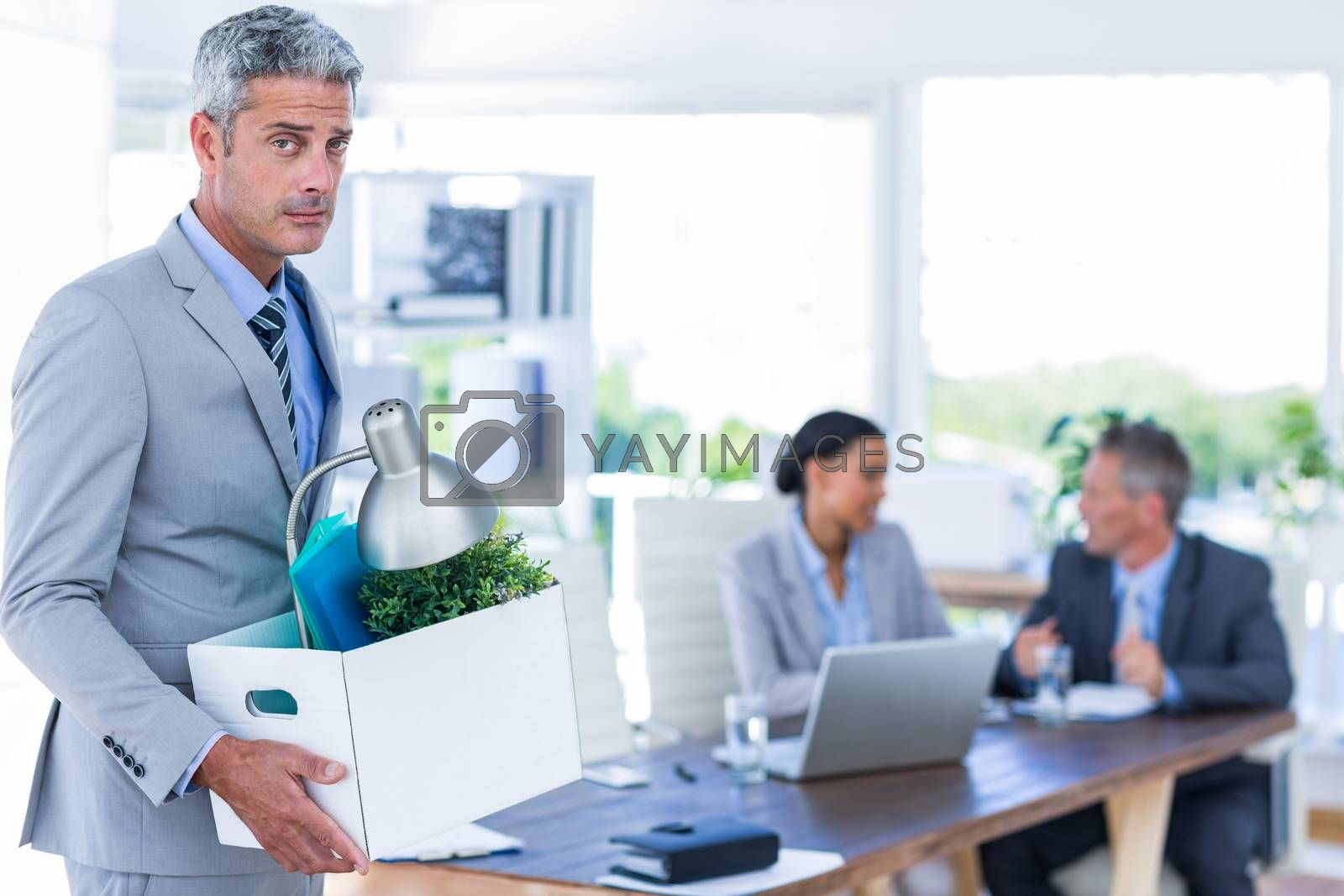 Royalty free image of Businessman holding box with his colleagues behind him  by Wavebreakmedia