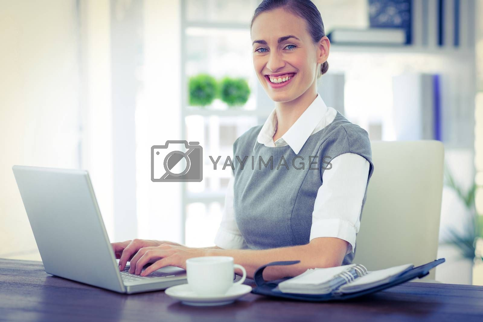 Royalty free image of Happy businesswoman working on laptop computer and looking at camera by Wavebreakmedia