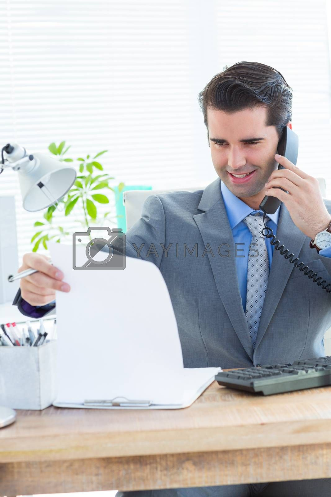 Royalty free image of Happy businessman phoning and looking note  by Wavebreakmedia
