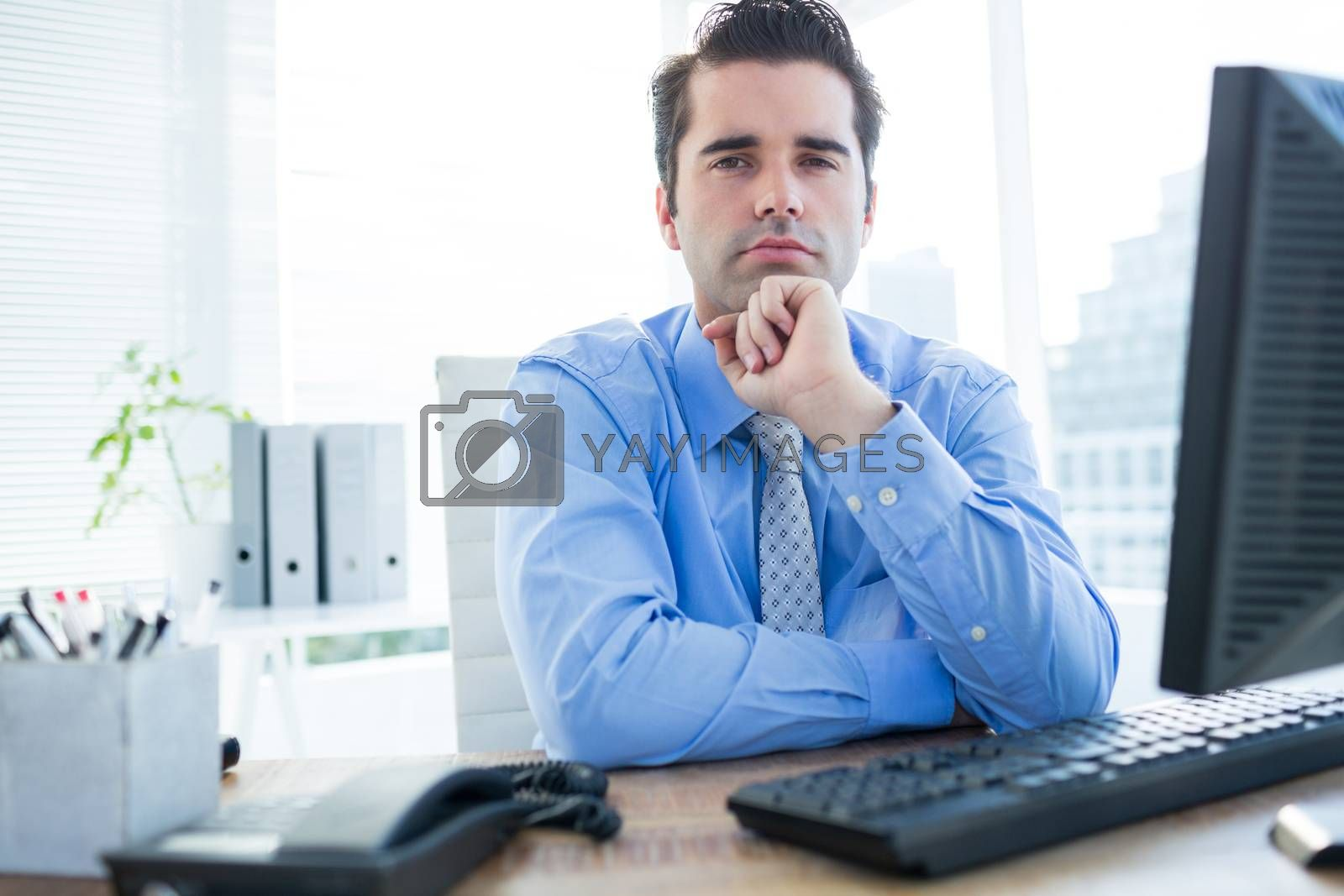 Royalty free image of Businessman sitting on an office chair with hand on chin by Wavebreakmedia