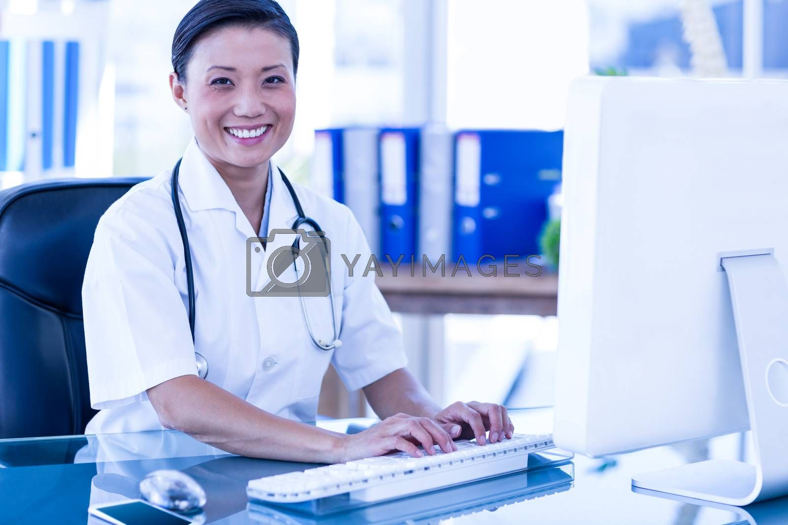 Royalty free image of Happy doctor using her computer and looking at camera by Wavebreakmedia