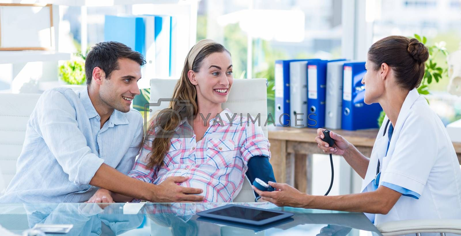 Royalty free image of Doctor taking the blood pressure of a pregnant patient with her husband by Wavebreakmedia