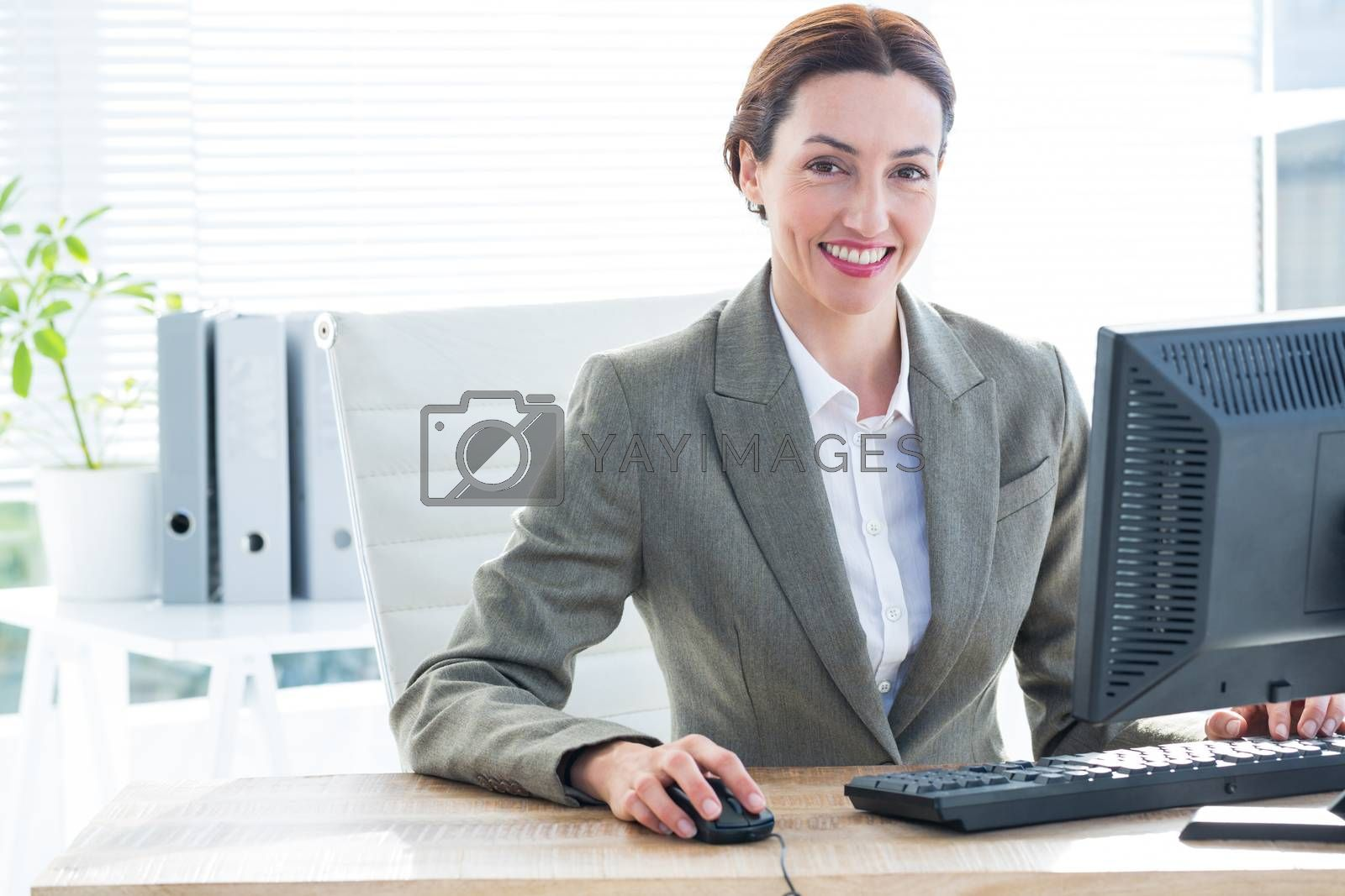 Royalty free image of Businesswoman using computer and smiling at camera  by Wavebreakmedia