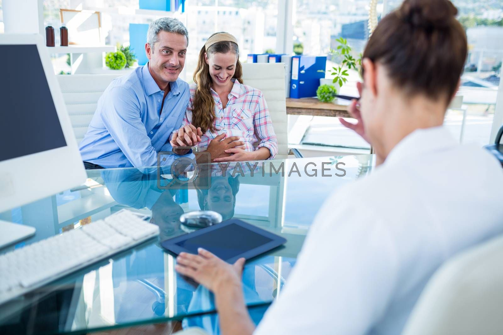 Royalty free image of Pregnant woman and her husband discussing with doctor by Wavebreakmedia