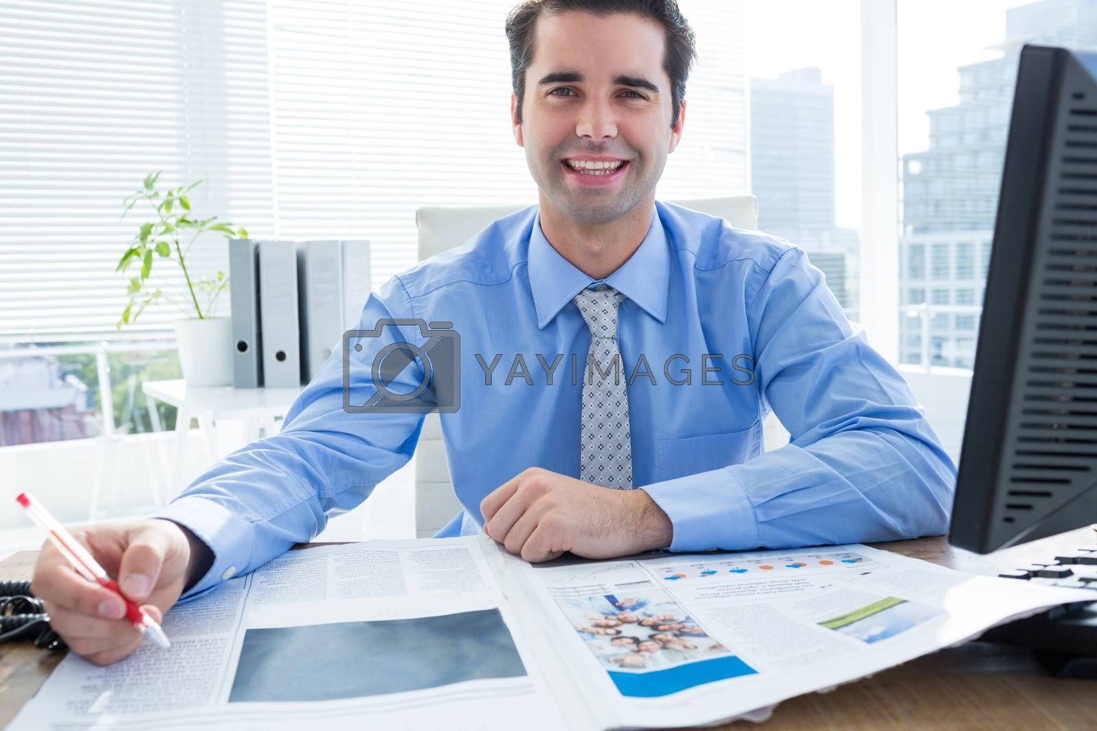Royalty free image of Happy businessman writing at his desk by Wavebreakmedia