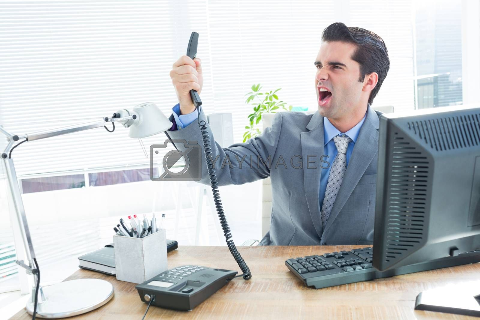 Royalty free image of Businessman shouting as he holds out phone at office by Wavebreakmedia